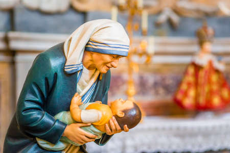 RAVENNA, ITALY - AUGUST 2, 2018: Statue of Mother Teresa of Calcutta holding a child inside  Church of Saint Mary of Suffrage in Ravenna Editorial