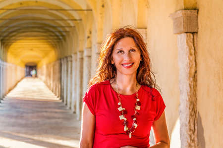menopausal woman smiling under long portico with vanishing point in the background Stock Photo