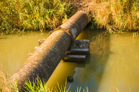 Old rusty and encrusted pipe for water sampling from irrigation channel Stok Fotoğraf