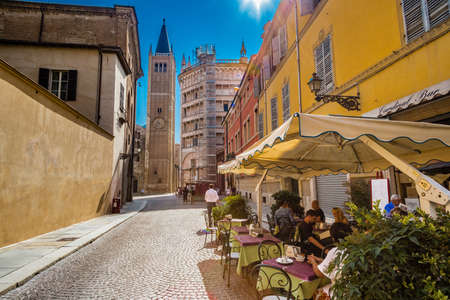 PARMA, ITALY – AUGUST 23, 2018: Tourists are walking and enjoying the charming historic lanes of Parma, elegant town in the Emilia-Romagna region of Northern Italy