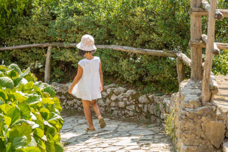 young child walking in cobblestone path Stock Photo