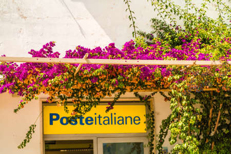 RAVELLO (SA), ITALY - AUGUST 29, 2018: a colorful bougainvillea glabra shadows the entrance of the Italian post office