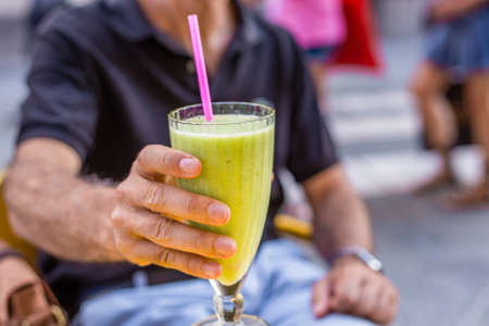 man offering Kiwi and Banana smoothie with straw