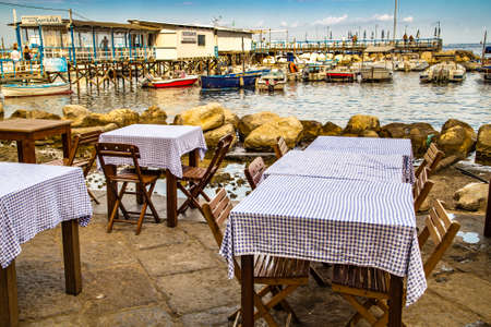 SORRENTO (NA), ITALY - SEPTEMBER 3, 2018: Checkered covering tablecloths on restaurant tables on the sea