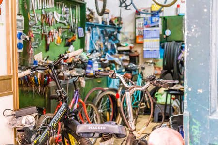 SORRENTO (NA), ITALY - SEPTEMBER 5, 2018: Bicycles are being repaired and hung in the workshop of bicycle mechanic