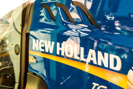 LUGO, ITALY - September 11, 2018: light enlightening NEW HOLLAND logo on a tractor body
