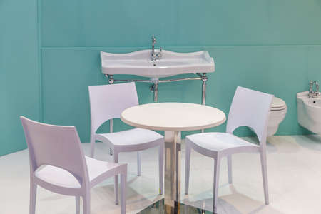 table and chairs in a bathroom with sink, bidet and toilet bowl