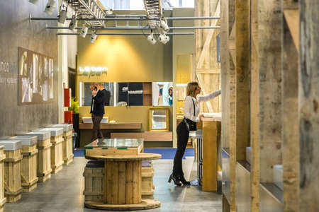 BOLOGNA (ITALY), SEPTEMBER 28, 2018: booth presenter is welcoming visitors among CERAMICA TECLA luxury washbasins at CERSAIE, international exhibition of ceramic tile and bathroom furnishings Editorial