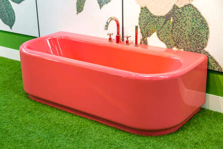 red bathtub on artificial green grass floor Foto de archivo - 110142769