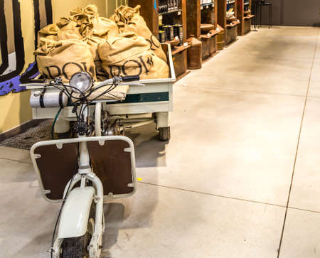 BOLOGNA, ITALY - OCTOBER 2, 2018: lights are enlightening old scooter with jute sacks at FICO EATALY WORLD, the largest agri-food park in the world