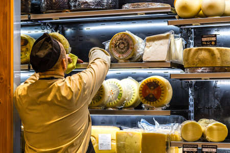BOLOGNA, ITALY - OCTOBER 2, 2018: salesman is organizing wheels of cheese fo sale at FICO EATALY WORLD, the largest agri-food park in the world