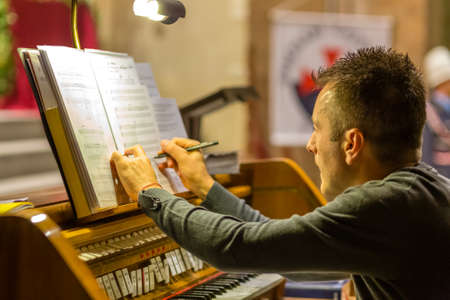 FORLI, ITALY - OCTOBER 26, 2018: Organist prepares the scores with the Templar cross in the background. Catholic Templar Knights participate in the ritual of Holy Mass