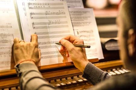 männliche Hand, die Musik auf weißem Notenblatt schreibt