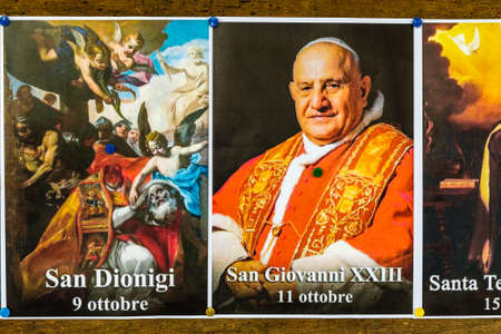 SAN BERNARDINO (RA), ITALY – OCTOBER 31, 2018: The priest put on the entrance of the church the images of the Saints to remind the religious connotation of Halloween Foto de archivo - 115508837