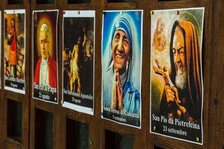 SAN BERNARDINO (RA), ITALY – OCTOBER 31, 2018: The priest put on the entrance of the church the images of the Saints to remind the religious connotation of Halloween Imagens - 115508872