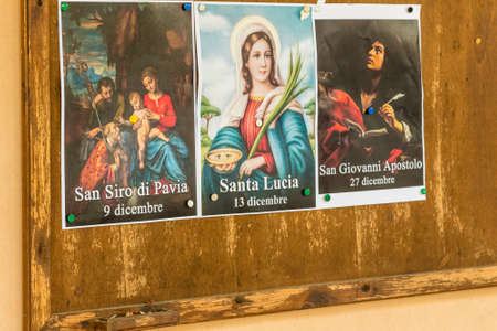 SAN BERNARDINO (RA), ITALY – OCTOBER 31, 2018: The priest put on the entrance of the church the images of the Saints to remind the religious connotation of Halloween Foto de archivo - 115508876