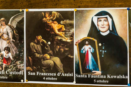 SAN BERNARDINO (RA), ITALY – OCTOBER 31, 2018: The priest put on the entrance of the church the images of the Saints to remind the religious connotation of Halloween Foto de archivo - 115508899