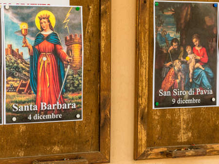 SAN BERNARDINO (RA), ITALY – OCTOBER 31, 2018: The priest put on the entrance of the church the images of the Saints to remind the religious connotation of Halloween Foto de archivo - 115508901