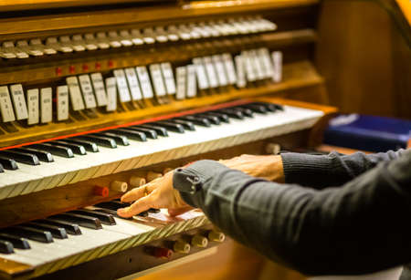 male hands playing organ keyboard in church Banco de Imagens - 115541485