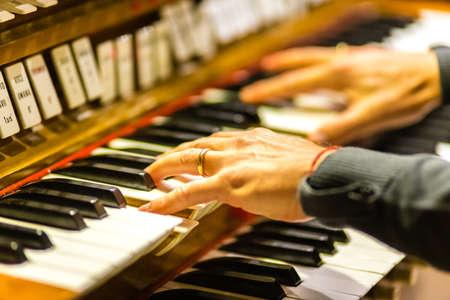 Manos masculinas tocando el teclado del órgano en la iglesia Foto de archivo