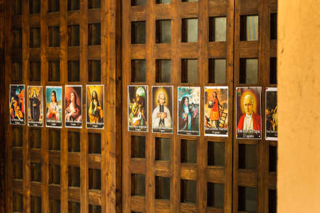 SAN BERNARDINO (RA), ITALY – OCTOBER 31, 2018: The priest put on the entrance of the church the images of the Saints to remind the religious connotation of Halloween Imagens - 115508918
