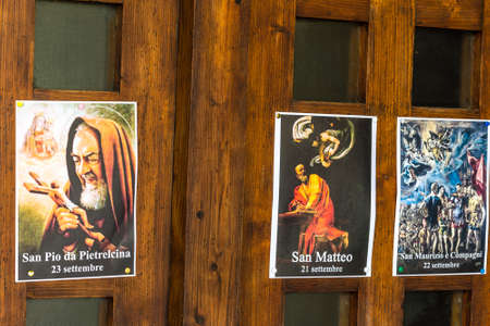SAN BERNARDINO (RA), ITALY – OCTOBER 31, 2018: The priest put on the entrance of the church the images of the Saints to remind the religious connotation of Halloween Imagens - 115508919