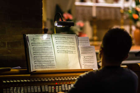 back of pianist looking at score on church organ
