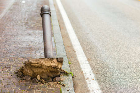 Uprooted and ripped through bollard in city street, Stockfoto