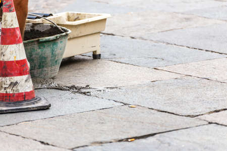 bricklayer repairing cobbled floor in urban square