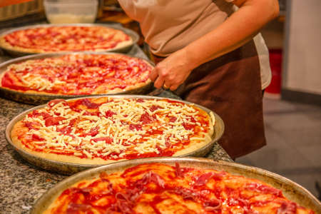 pizza maker at work preparing variety of pizzas
