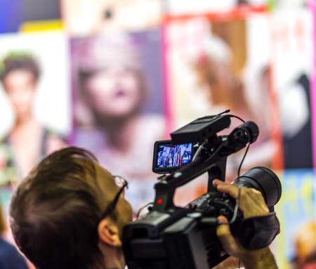 Cameraman recording fashion event with professional shoulder camera