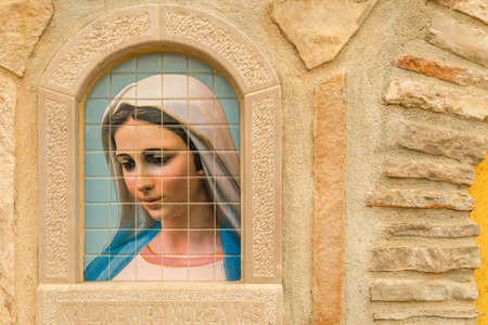 Medjugorje, Bosnia and Herzegovina - November 3, 2018: sunlight is enlightening painting of the Blessed Virgin Mary on tiles