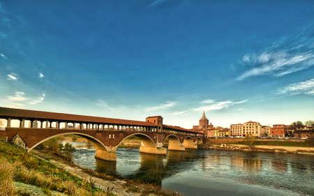 überdachte Brücke über das fließende Wasser des Tessin in Pavia in Italien