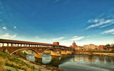covered bridge over the flowing waters of the Ticino river in Pavia in Italy