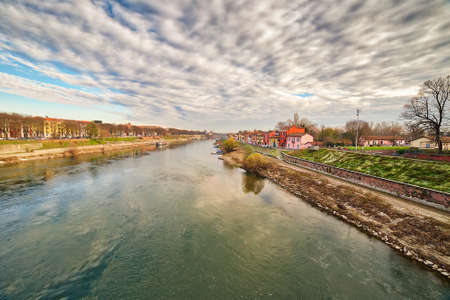 flowing waters of the Ticino river near colorful houses in Pavia in Italy Banco de Imagens