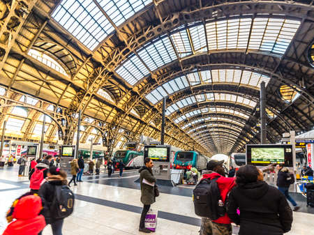 MILANO, ITALY - DECEMBER 12, 2018: travelers watching the trains departing at Milano Centrale station Stock Photo - 115572604