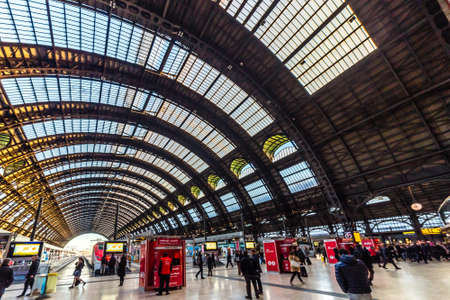 MILANO, ITALY - DECEMBER 12, 2018: travelers standing, walking and watching the trains departing at Milano Centrale station Stock Photo - 115576803