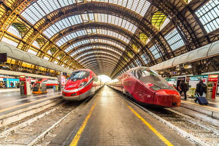 MILANO, ITALY - DECEMBER 12, 2018: TRENITALIA FRECCIAROSSA and NTV ITALO  trains waiting at Milano Centrale station 新聞圖片