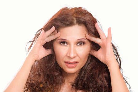 woman with headache holding her head