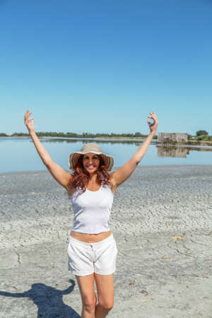 sun tanned girl with wide hat smiling on dry seaside and raising arms