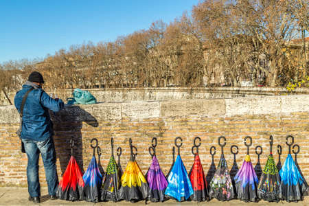 ROME, ITALY - JANUARY 4, 2019: street vendor selling colorful umbrellas to tourists on Pons Fabricius, the oldest Roman bridge in Rome