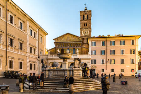 ROME, ITALY - JANUARY 2, 2019: tourists resting and relaxing on the fountain in Piazza Santa Maria in Trastevere Editorial