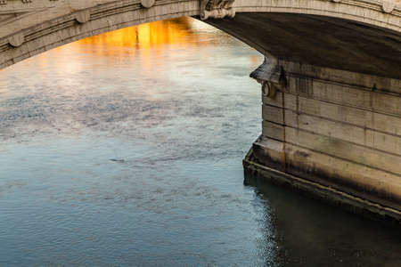 waters of river flowing under ancient bridge Stock Photo