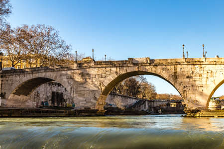 ROME, ITALY - JANUARY 4, 2019: waters of Tiber river is flowing under ancient bridge