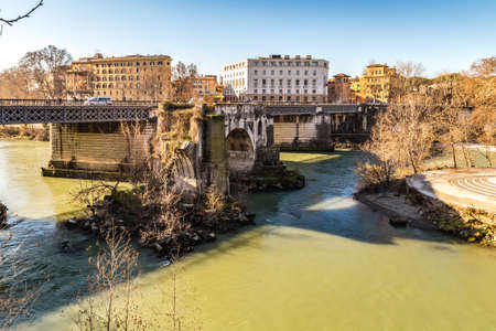 ROME, ITALY - JANUARY 4, 2019: waters of Tiber River are flowing under the Palatino bridge, in front of Broken bridge, wonder of Rome Editorial