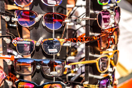 ROME, ITALY - JANUARY 4, 2019: sun light is enlightening colorful glasses for sale on racks in street shop