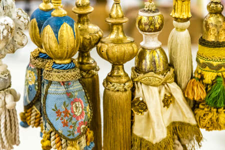 CESENA, ITALY - NOVEMBER 18, 2018: lights are enlightening the tassels of curtain for sale in Antiques Fair