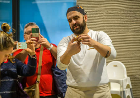 BOLOGNA, ITALY - DECEMBER 16, 2018: tourists taking photo of cook teaching how to make pasta at FICO Eataly World, the largest gourmet agri-food park in the world