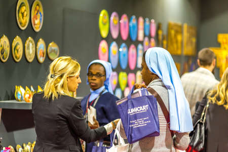 BOLOGNA, ITALY - FEBRUARY 18, 2019: Booth presenter talking with visitor at stand of EGIM in DEVOTIO Religious products and service exhibition