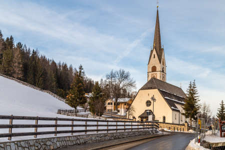 Catholic church in Alpine snowy panorama